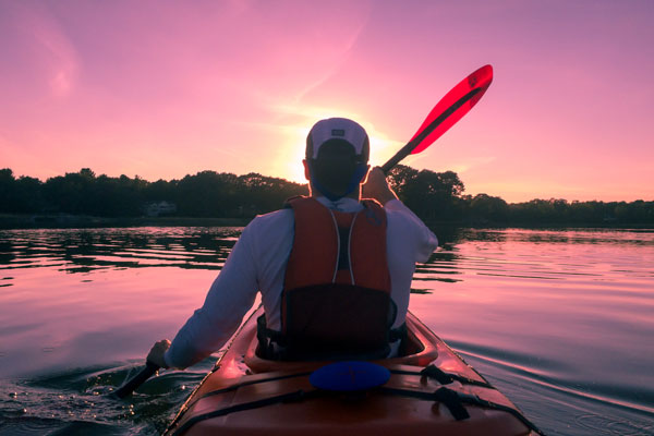 Life Coaching - Man in kayak in front of sunset