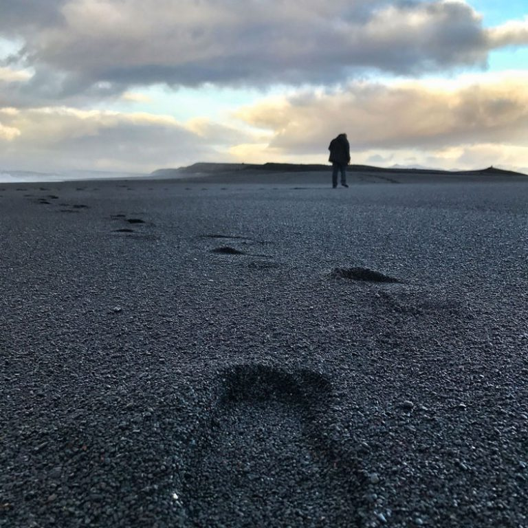 Grief Recovery - Person walking on the beach with footprints in the sand